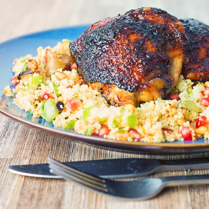 Square close up image of glazed harissa chicken thighs on a bed of couscous served on a blue plate