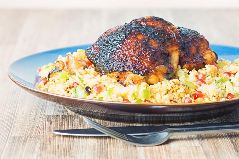 Landscape image of glazed harissa chicken thighs on a bed of couscous served on a blue plate