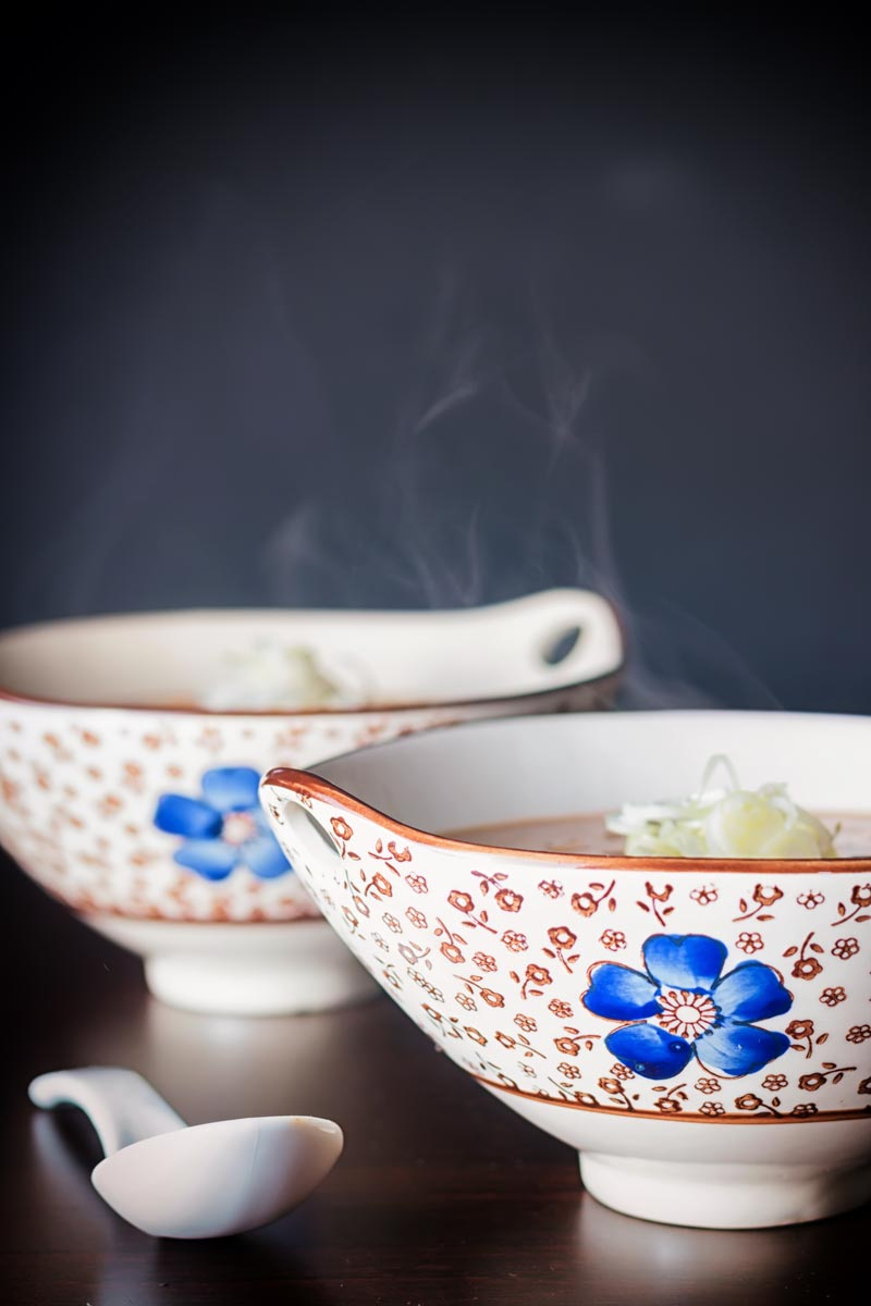 A steaming bowl of soup in an Asian soup bowl decorated with a blue flower