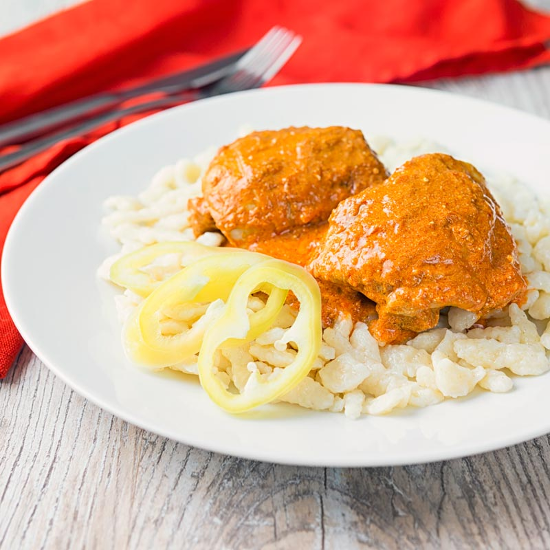 Square image of Hungarian Chicken Paprikash cooked with chicken thighs on buttered nokedli on a white plate