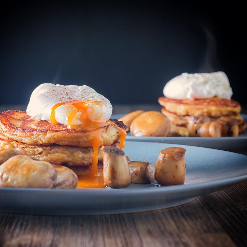 A perfectly cooked poached egg sat on a stack of Irish boxty potato pancakes