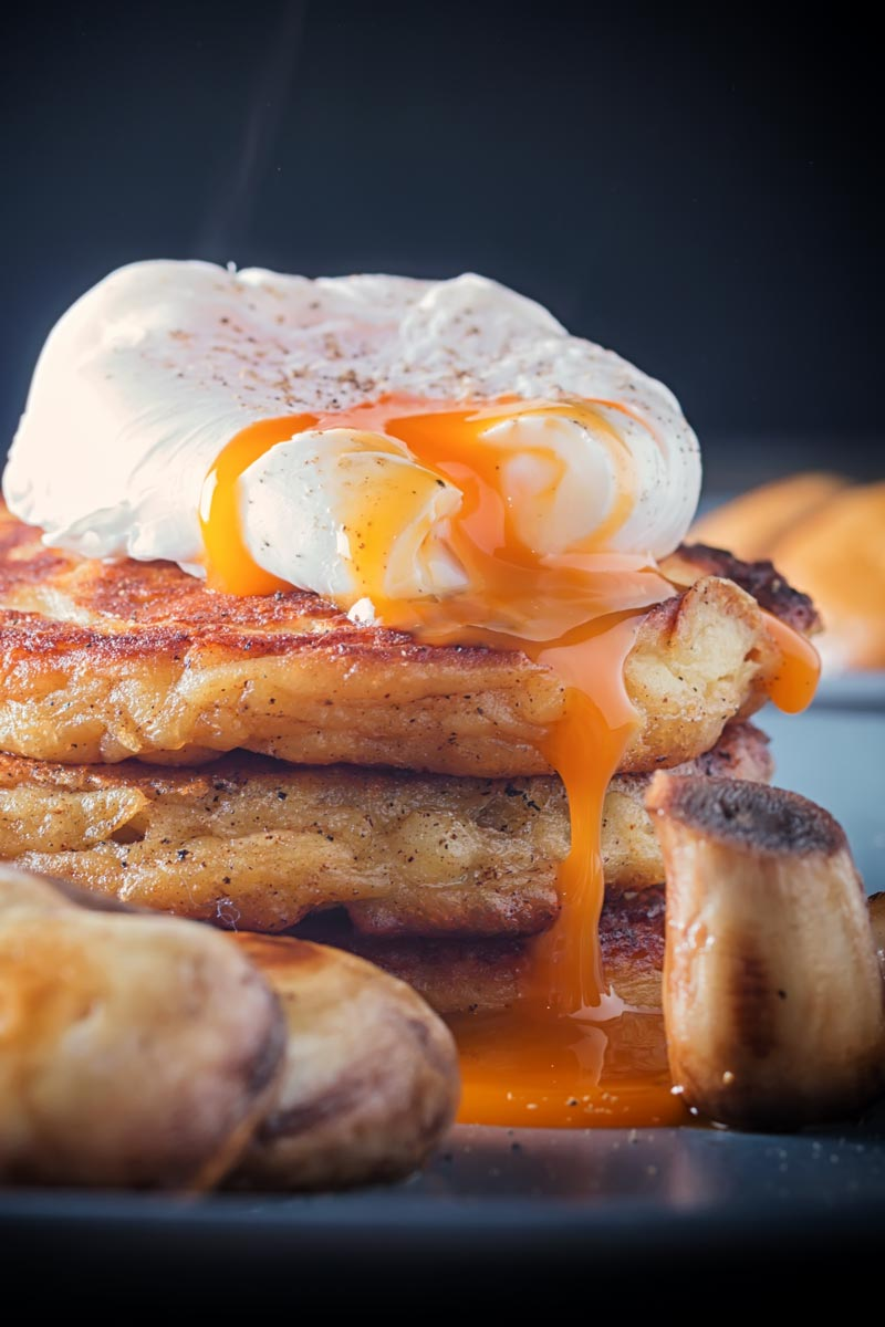 Stacked Irish Boxty pancakes with a perfectly poached eggwith a dripping golden egg yolk