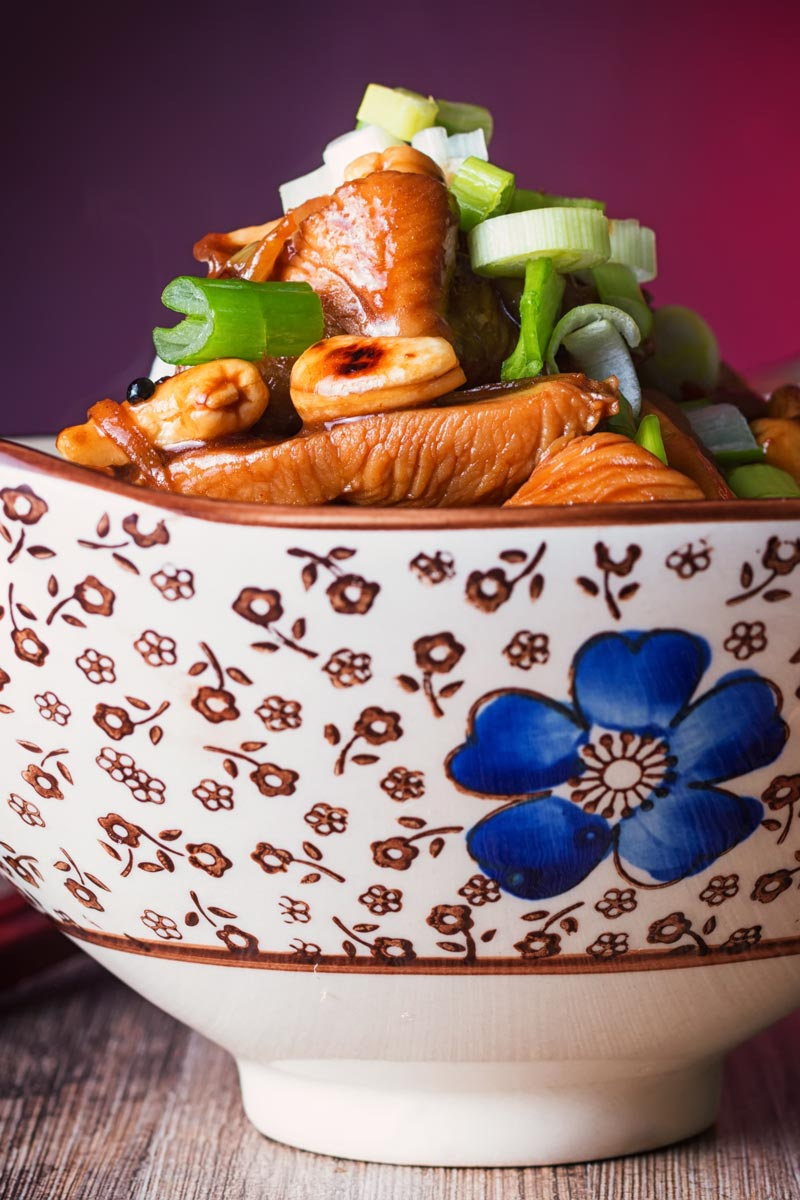 Tall close up image of a bowl of kung pao chicken in Asian style bowl featuring a blue flower.