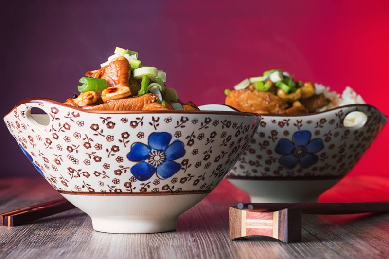 Landscape image of two bowls of kung pao chicken in Asian style bowls featuring a blue flower.