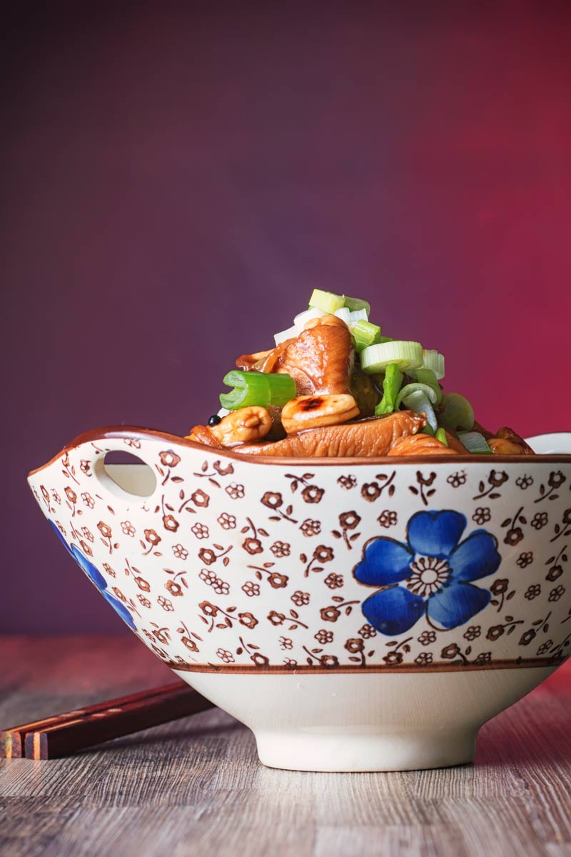 Portrait image of a bowl of kung pao chicken in Asian style bowl featuring a blue flower.