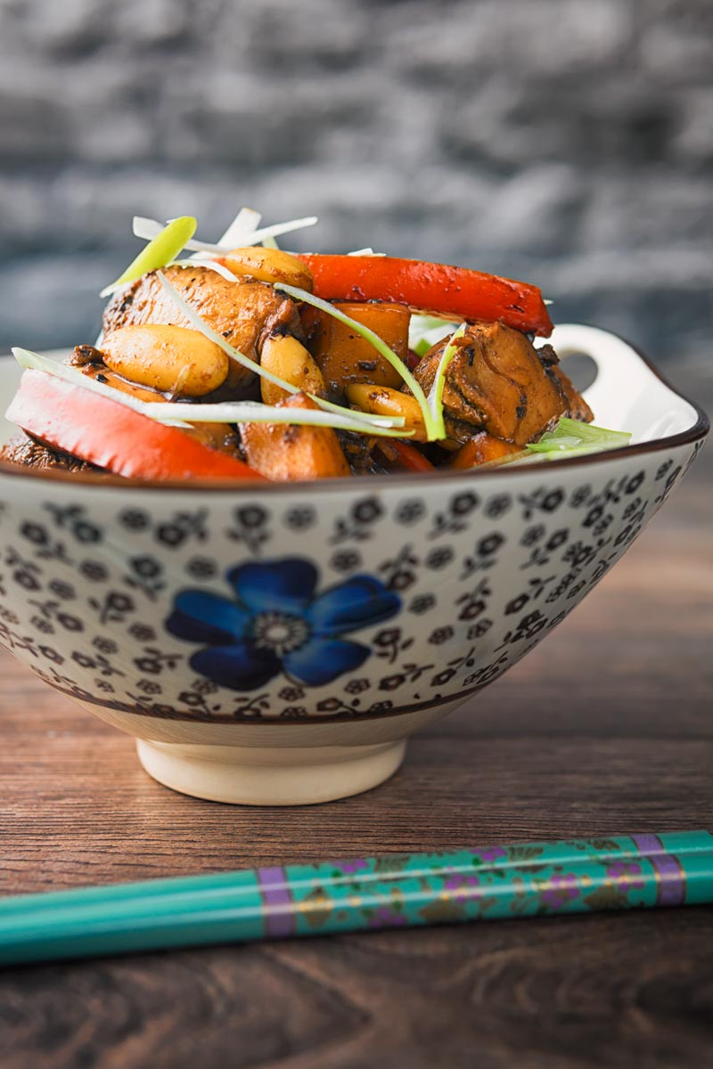 Tall image of a mango chicken stir fry in an Asian style sup bowl with a blue flower
