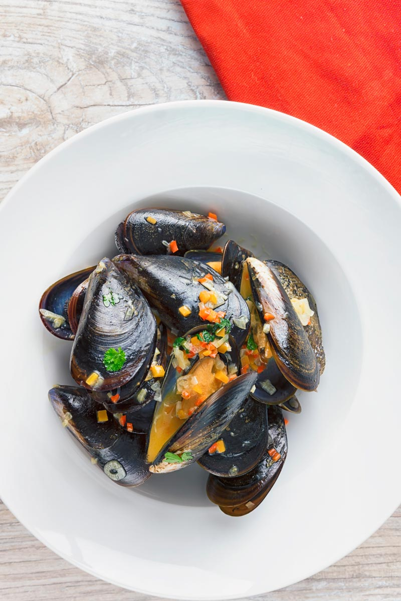 Tall image of steamed mussels in a white wide rimmed bowl taken from above