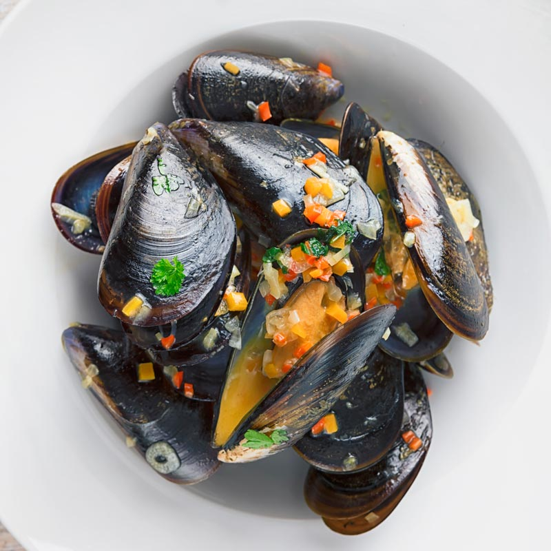 Overhead image of steamed mussels in a white bowl