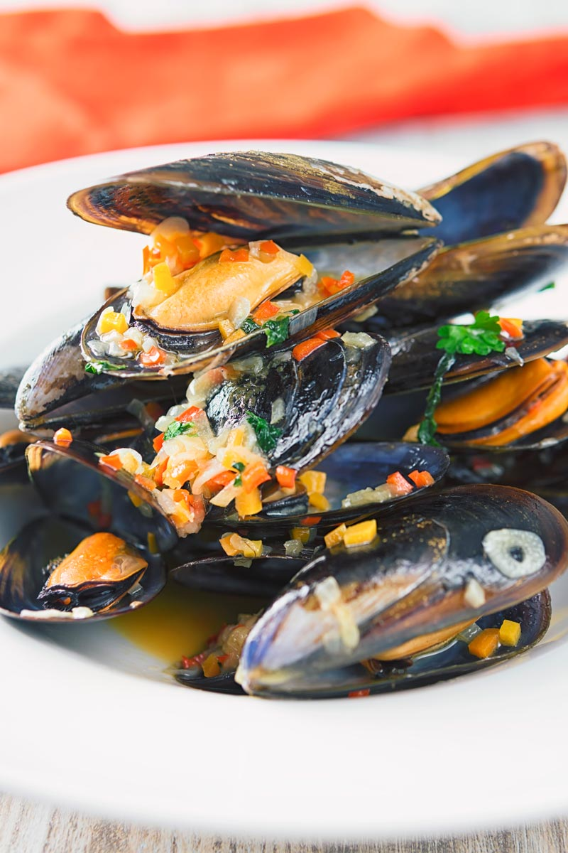 Beer steamed mussels in their shells piled in a while bowl