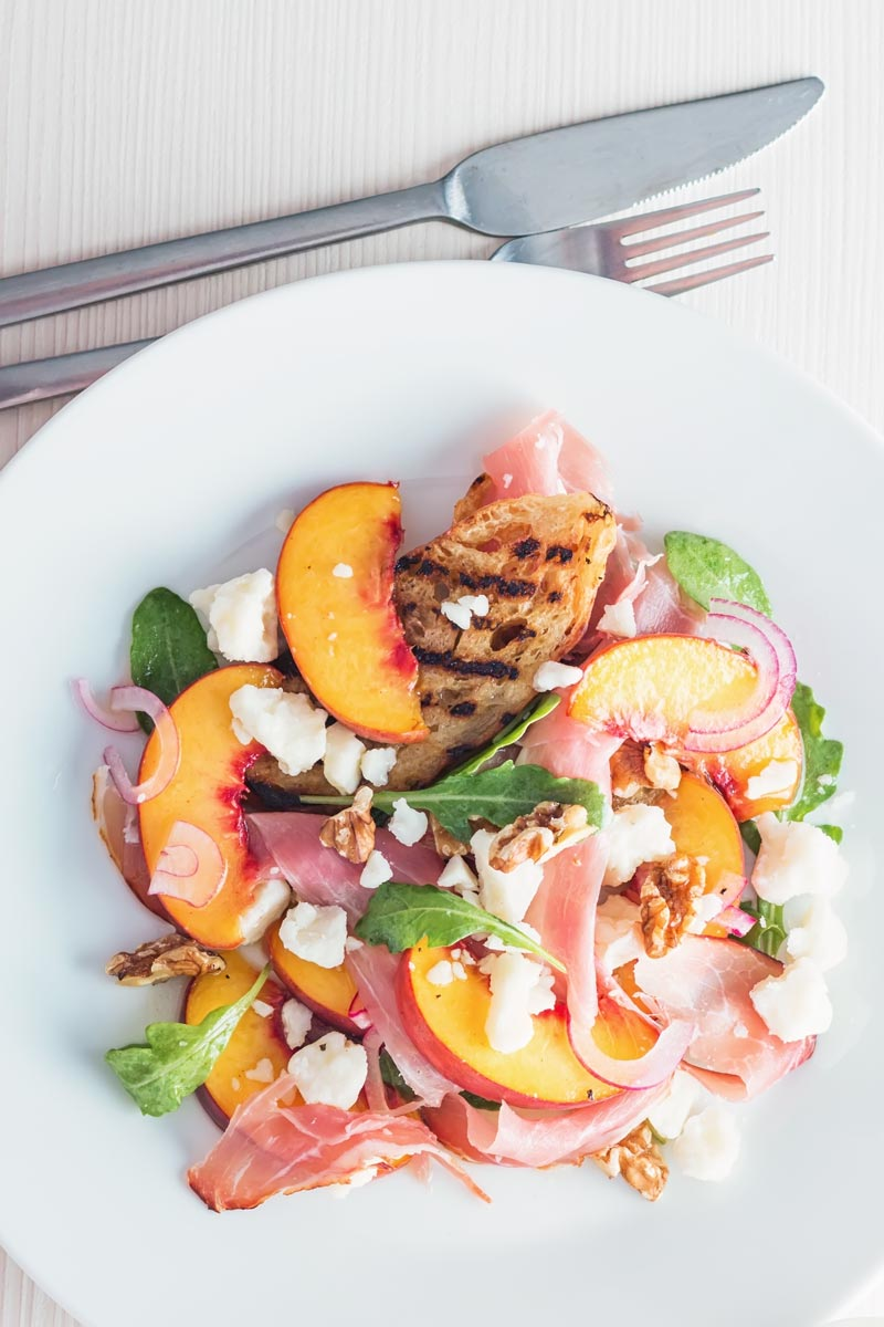 Pickled peaches and griddled bread in a  ham and cheese salad photographed from above