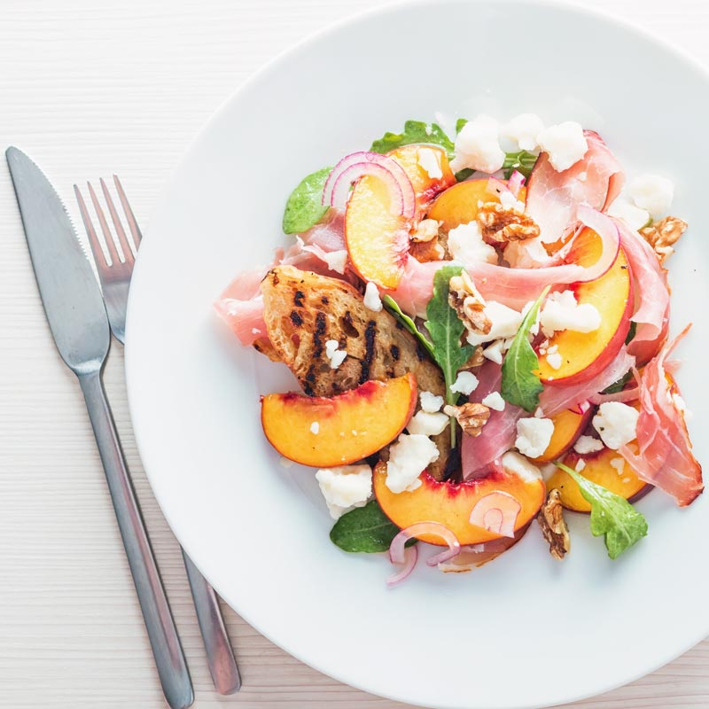 Square image of a ham and cheese salad with pickled peaches taken from above