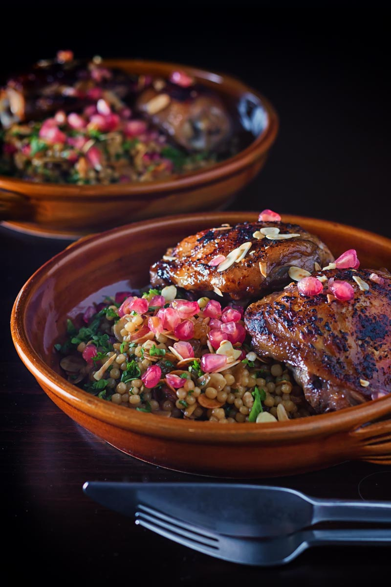 Glazed pomegranate chicken thighs with pomegranate seeds and almonds on couscous in an earthenware bowl on a dark background