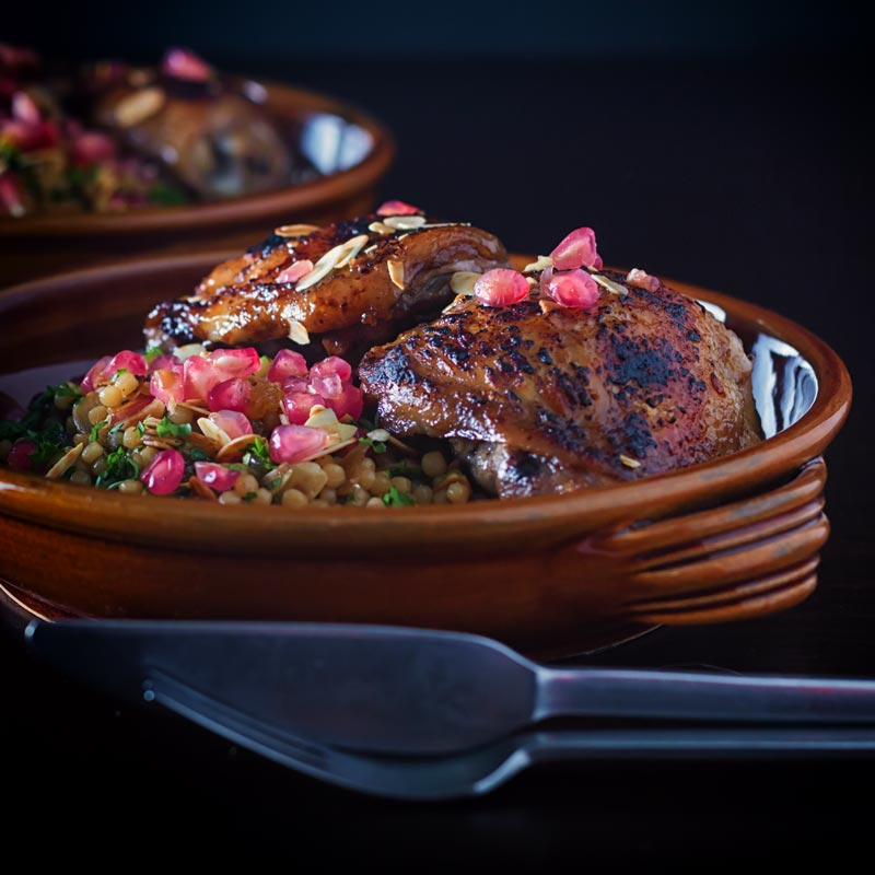 Pomegranate chicken thighs, a truly delightful, exotic but simple meal using pomegranate molasses and pomegranate seeds served with a simple Israeli Couscous side dish.