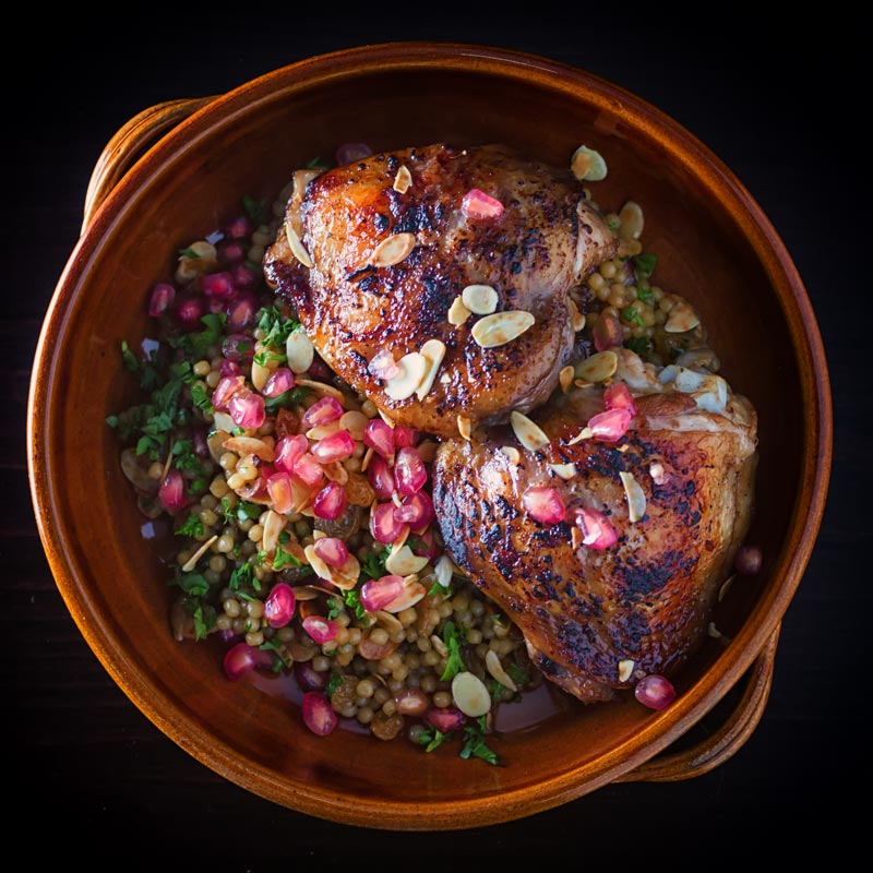 Square image of glazed pomegranate molasses chicken thighs with Israeli couscous in an earthenware bowl