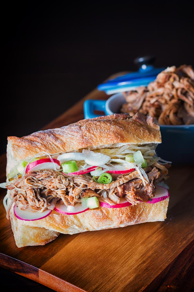 Tall image of Slow cooker pulled pork in a sandwich with a bowl of pulled pork on the side