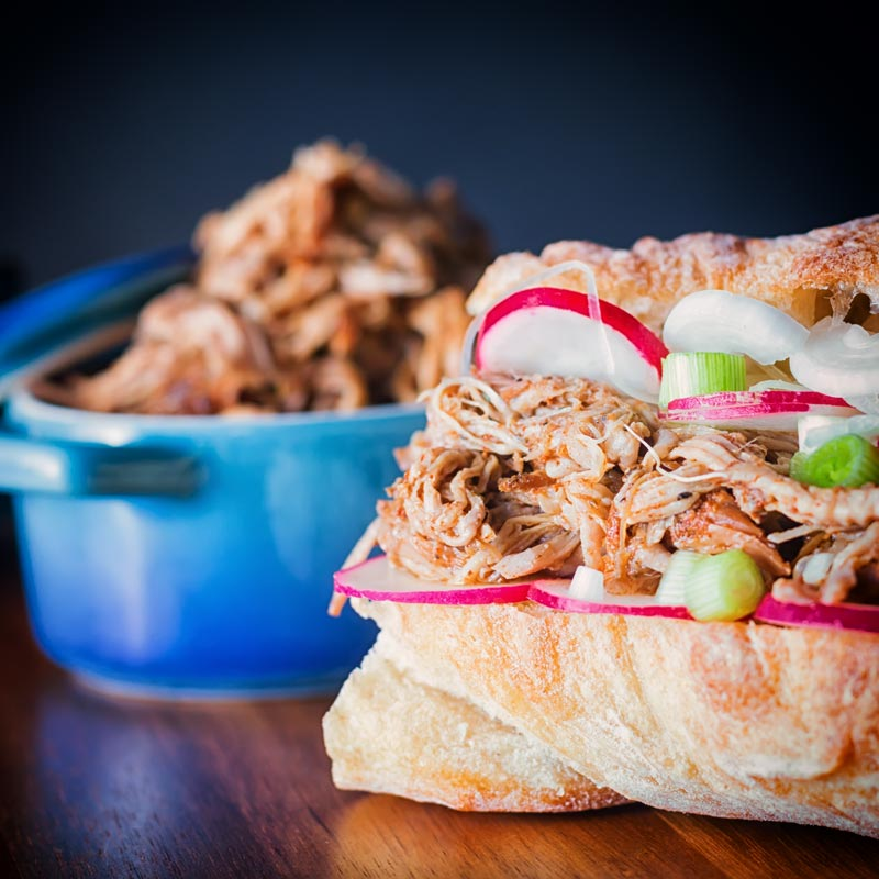 Close up square image of a pulled pork sandwich with slow cooker pulled pork in a bowl behind in a square bowl.
