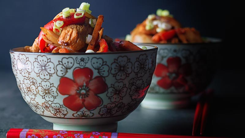 Two bowls of chicken with black bean sauce with red peppers and carrots served in an Asian bowl decorated with a red flower