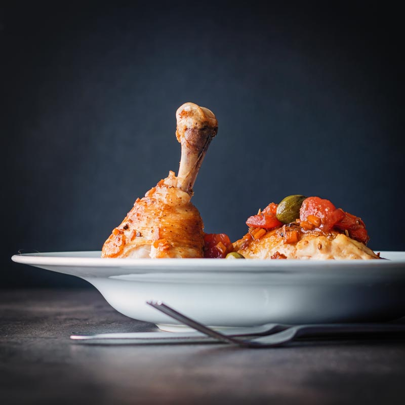 Square picture of a roast chicken leg with capers and tomatoes in a white bowl against a dark back drop