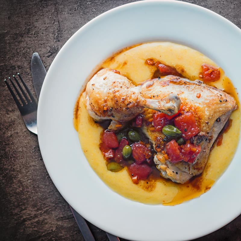 Over head square picture of a roast chicken leg with tomatoes and capers on a bed of polenta in a white bowl