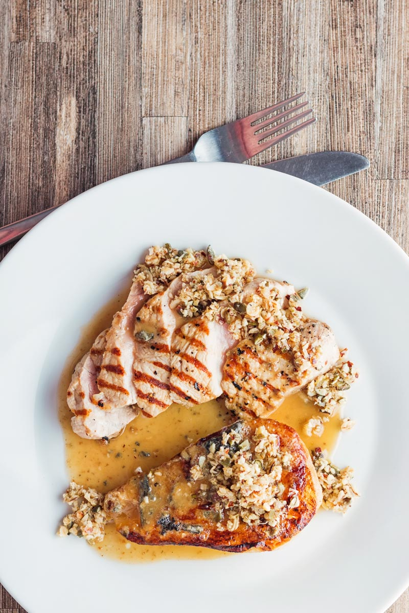 Tall image of roasted pears with blue cheese and a savoury crumble in a cider sauce and pork loin steak on a white plate
