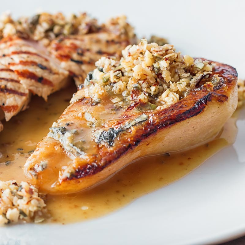 Close up square image of roasted pears with blue cheese and a savoury crumble in a cider sauce