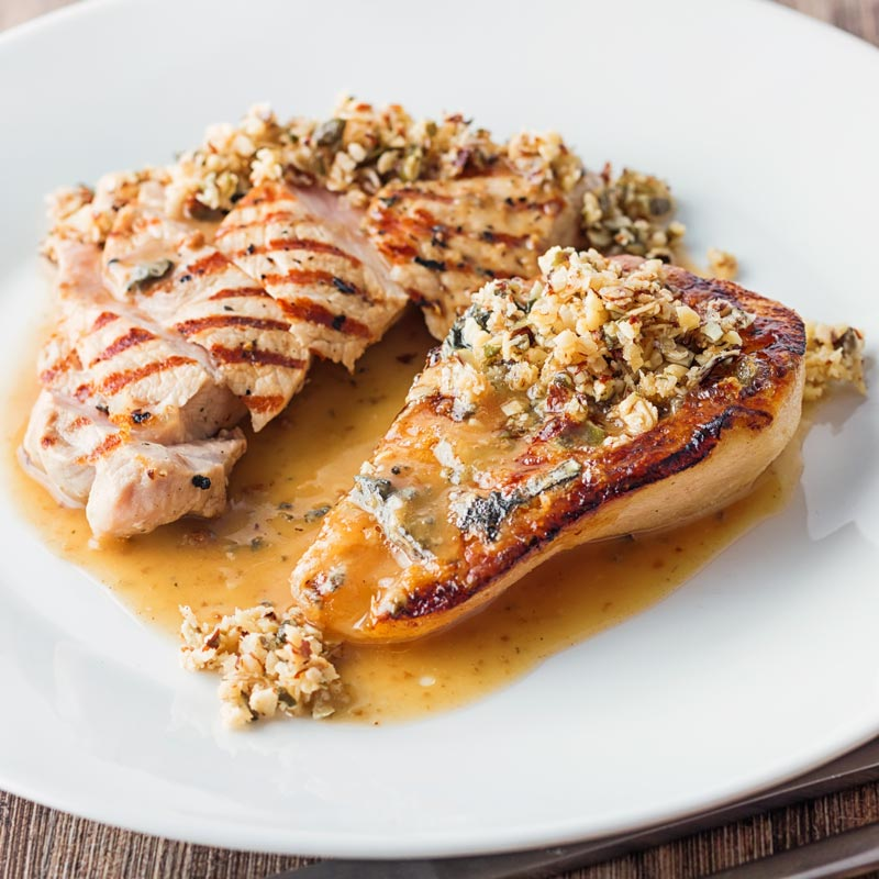 Square image of roasted pears with blue cheese and a savoury crumble and pork loin steak in a cider sauce on a white plate