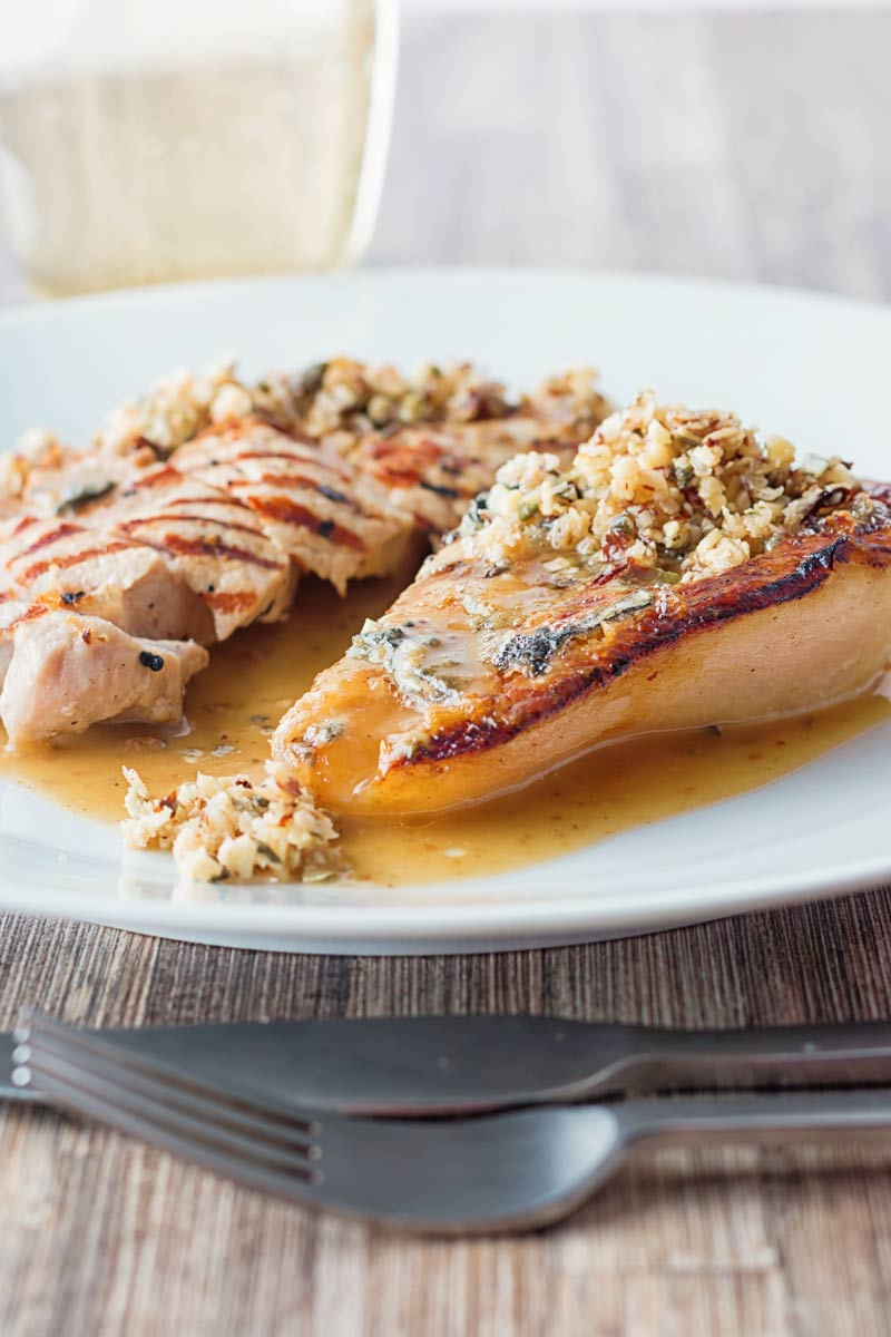 Tall image of roasted pears with blue cheese and a savoury crumble in a cider sauce on a white plate
