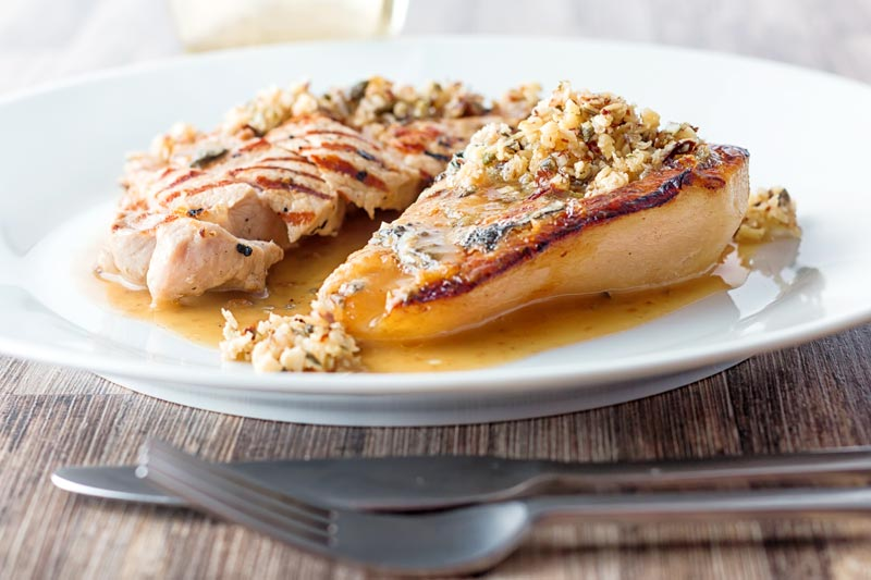 Landscape image of roasted pears with blue cheese and a savoury crumble and pork loin steak in a cider sauce on a white plate