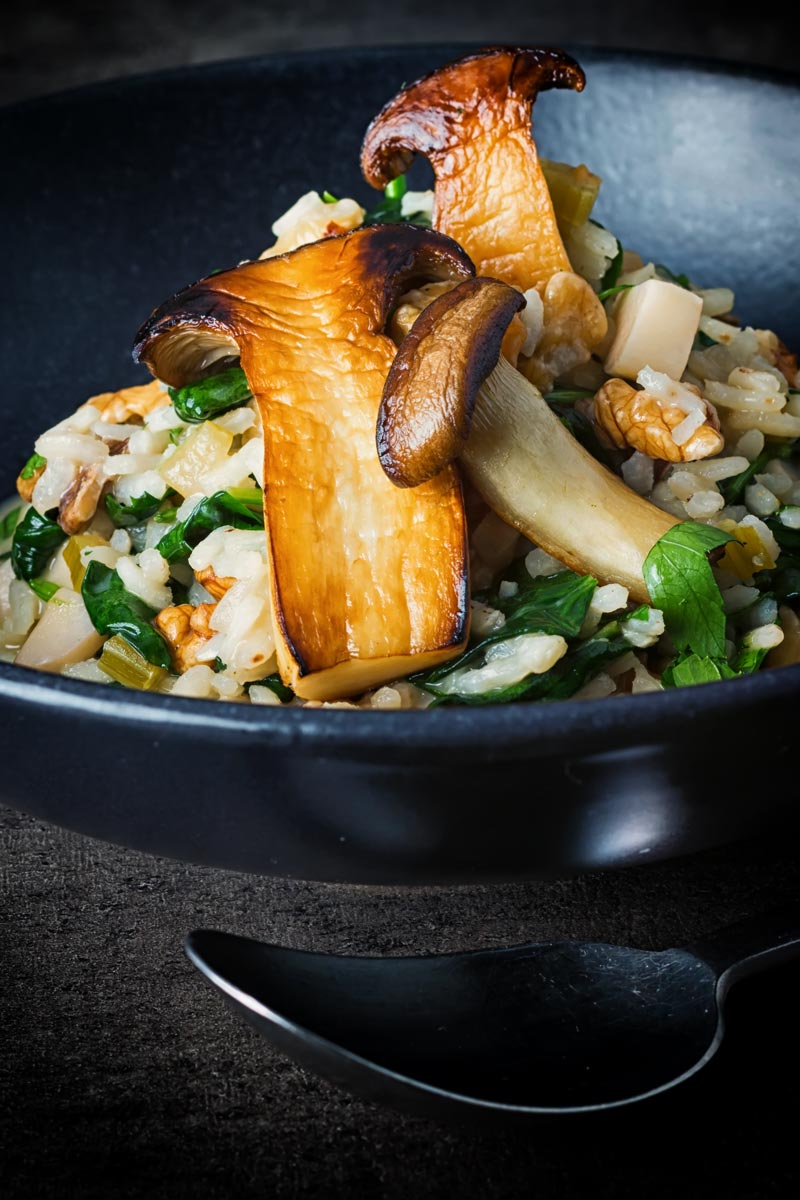 Tall image of a spinach risotto with sauteed french horn or king oyster mushrooms in a black bowl