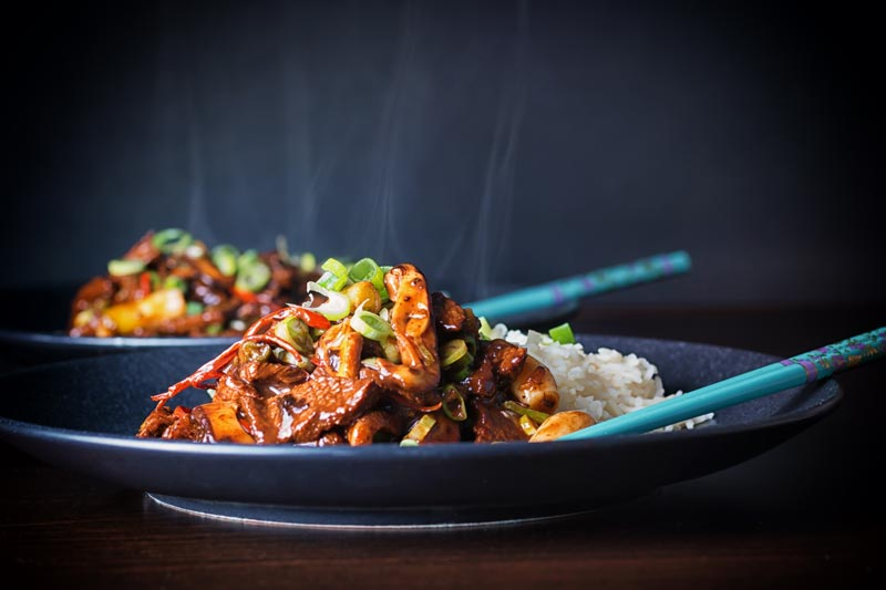 Steaming hot landscape image of beef stir fry with shiitkae mushrooms and shredded chili against a dark backdrop