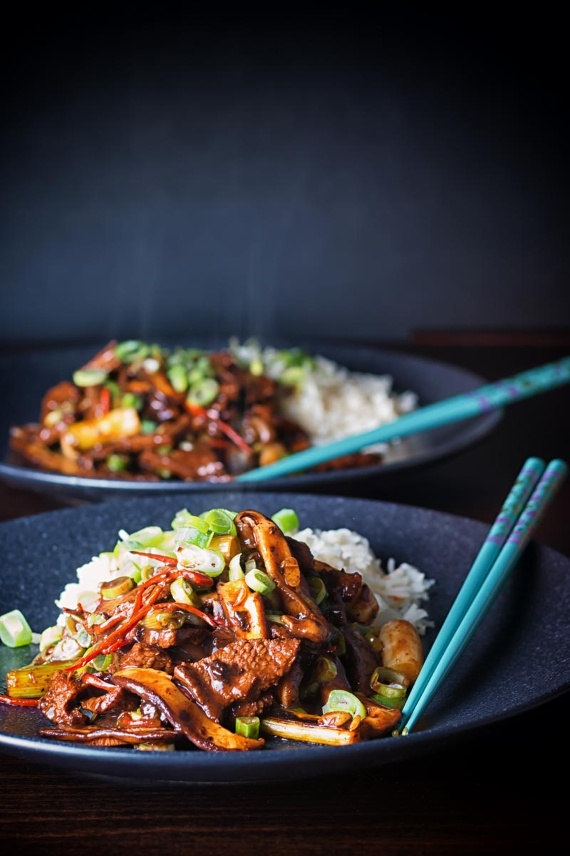 Portrait image of two portions of beef stir fry served with rice on black plates with pale blue chopsticks