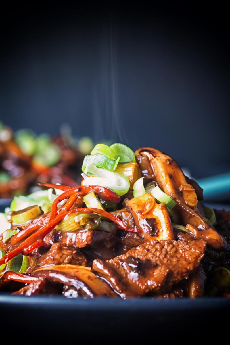 Close up portrait image of a steaming portion of beef stir fry with shiitake mushrooms and shredded chili against a dark backdrop