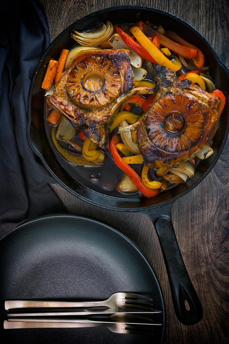 Portrait image of two Sweet and sour pork chops sat on a bed of vegetables in a cast iron skillet take from above.