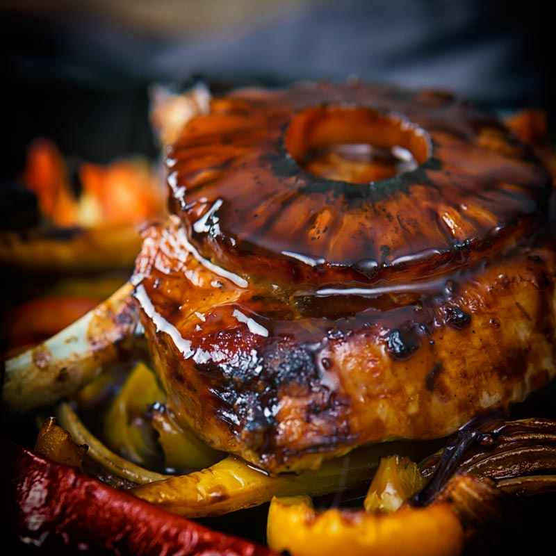 A glazed pineapple ring on a sweet and sour pork chop in close up