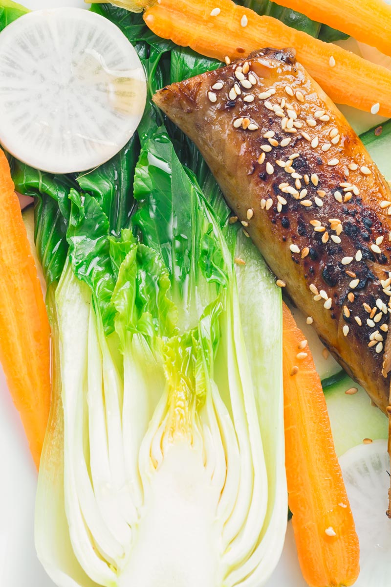 A broiled teriyaki smoked mackerel fillet with bok choi, white radish and pickled carrot close up
