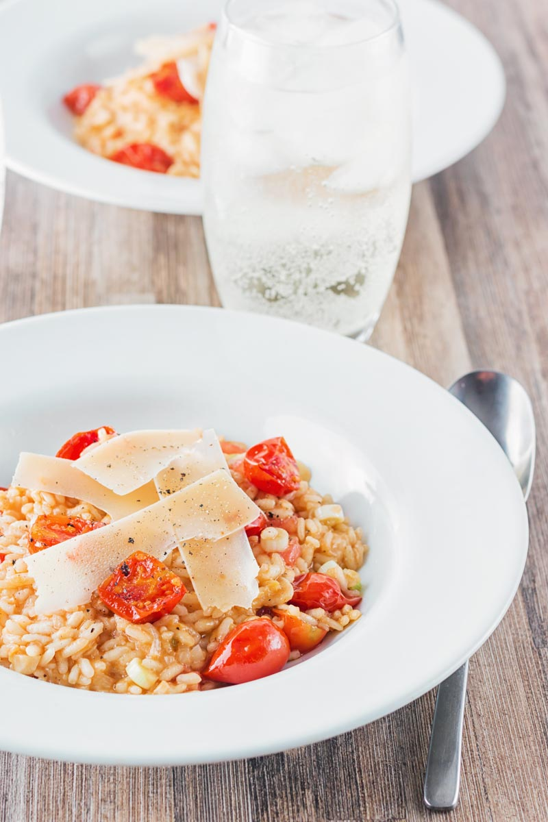 Tomato risotto with roasted cherry tomatoes in a white bowl and glass of spritzer