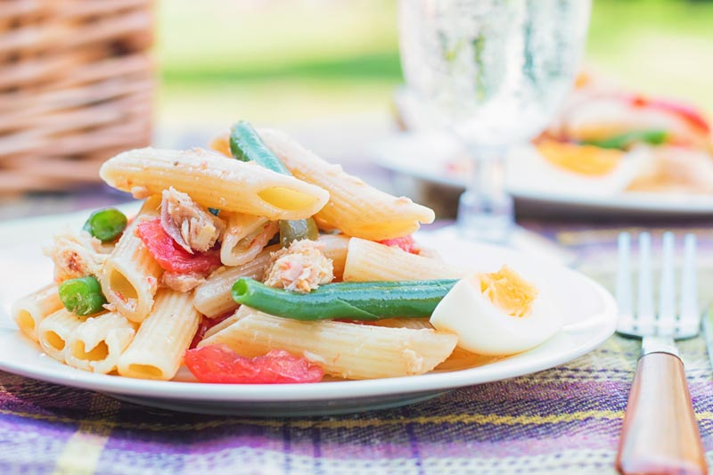 Landscape image of a Tuna pasta salad in a picnic setting with a boiled egg