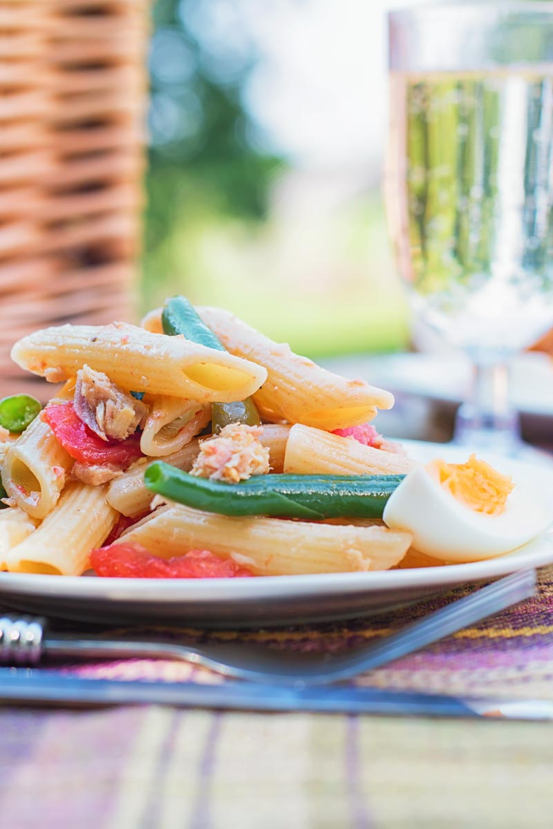 Tall image of a Tuna pasta salad in a picnic setting with a boiled egg