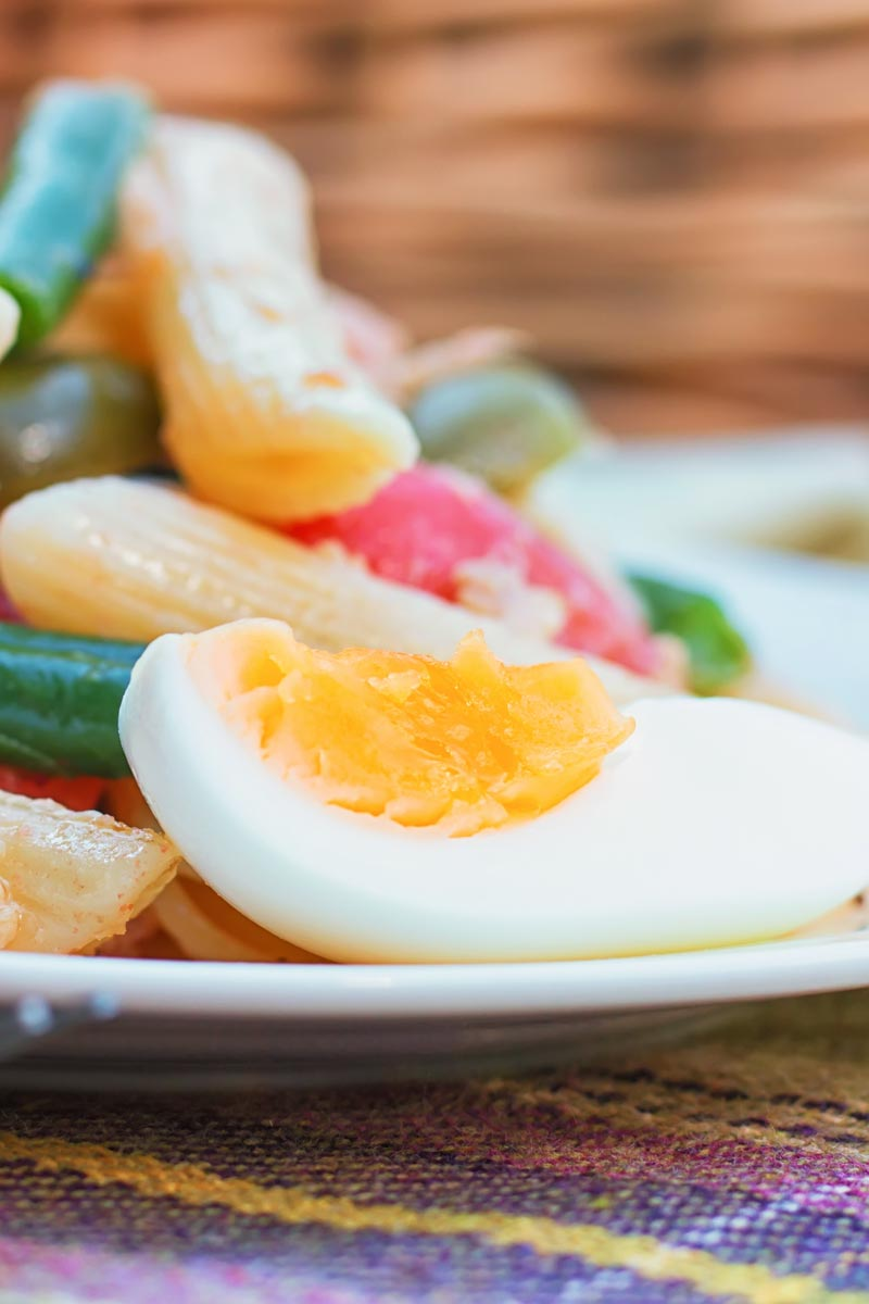 Close up of a quartered boiled egg in a pasta salad