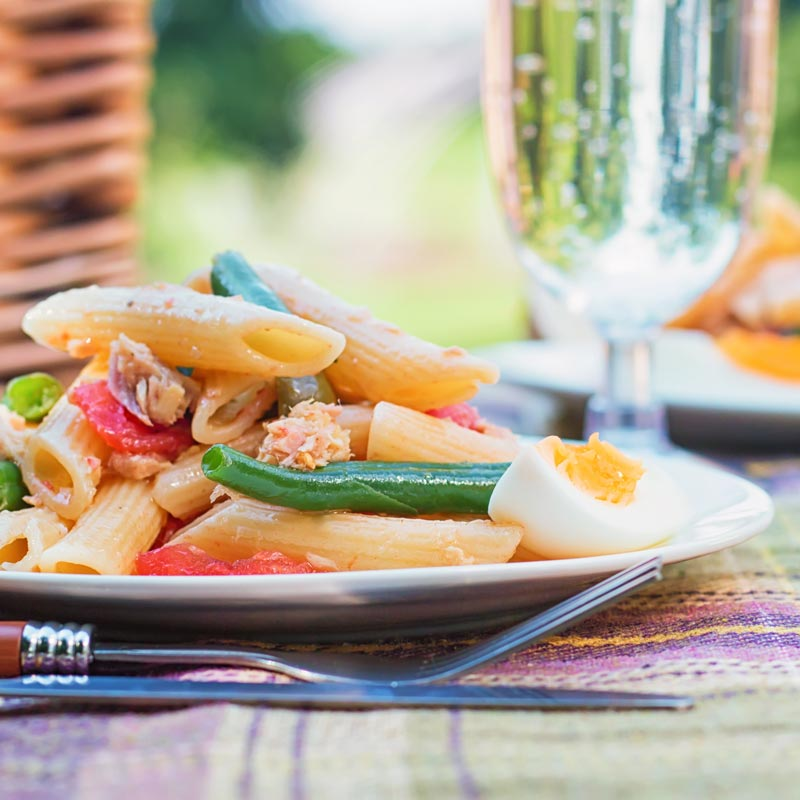 Square image of a Tuna pasta salad in a picnic setting with a boiled egg