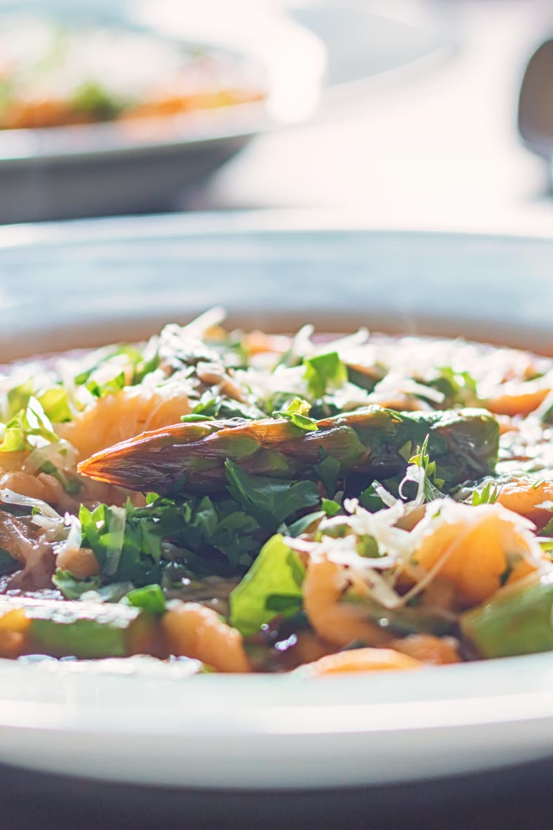Portrait close up back lit image of a thick asparagus and pasta soup in a white bowl with herbs and parmesan cheese