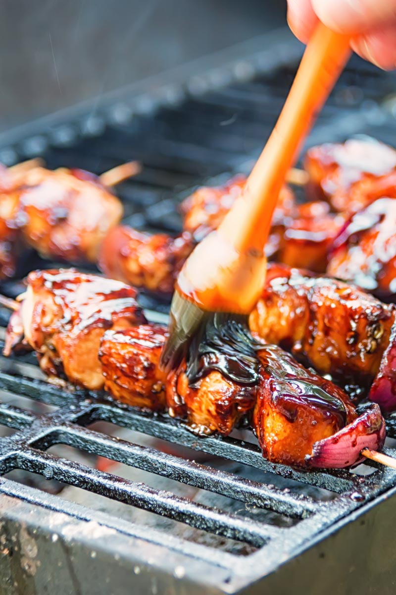 Pineapple chicken kebabs being coated in a bbq sauce cooking on a grill.