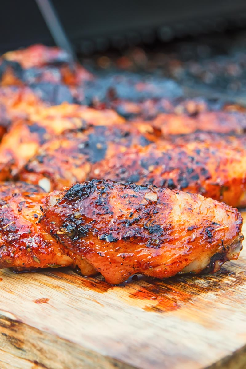Sriracha glazed grilled chicken wings on a wooden chopping board with a bbq in the background