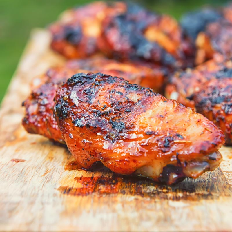 Close up square image of sriracha glazed grilled chicken wings on a wooden chopping board