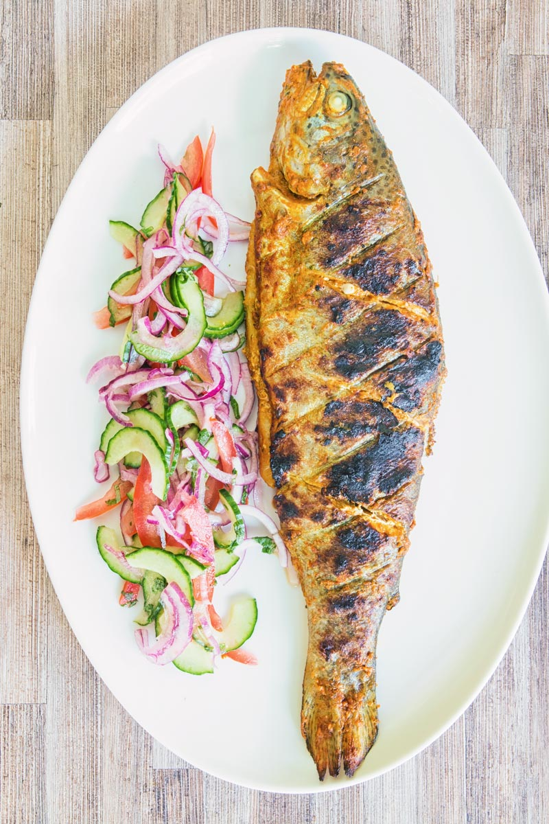 A whole BBQ tandoori fish with a kachumber salad on an oval plate taken from above