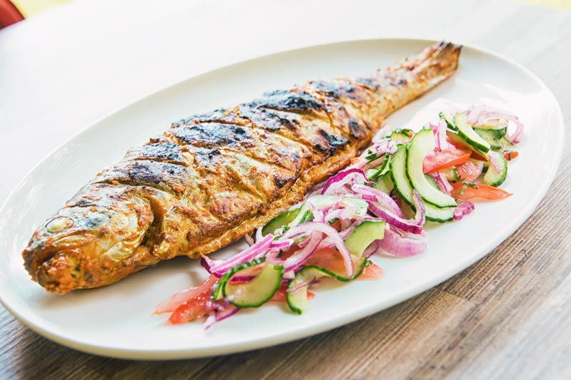 Landscape image of a whole BBQ tandoori fish with a kachumber salad on an oval plate