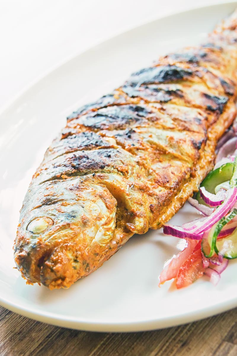 A whole BBQ tandoori fish with a kachumber salad on an oval plate