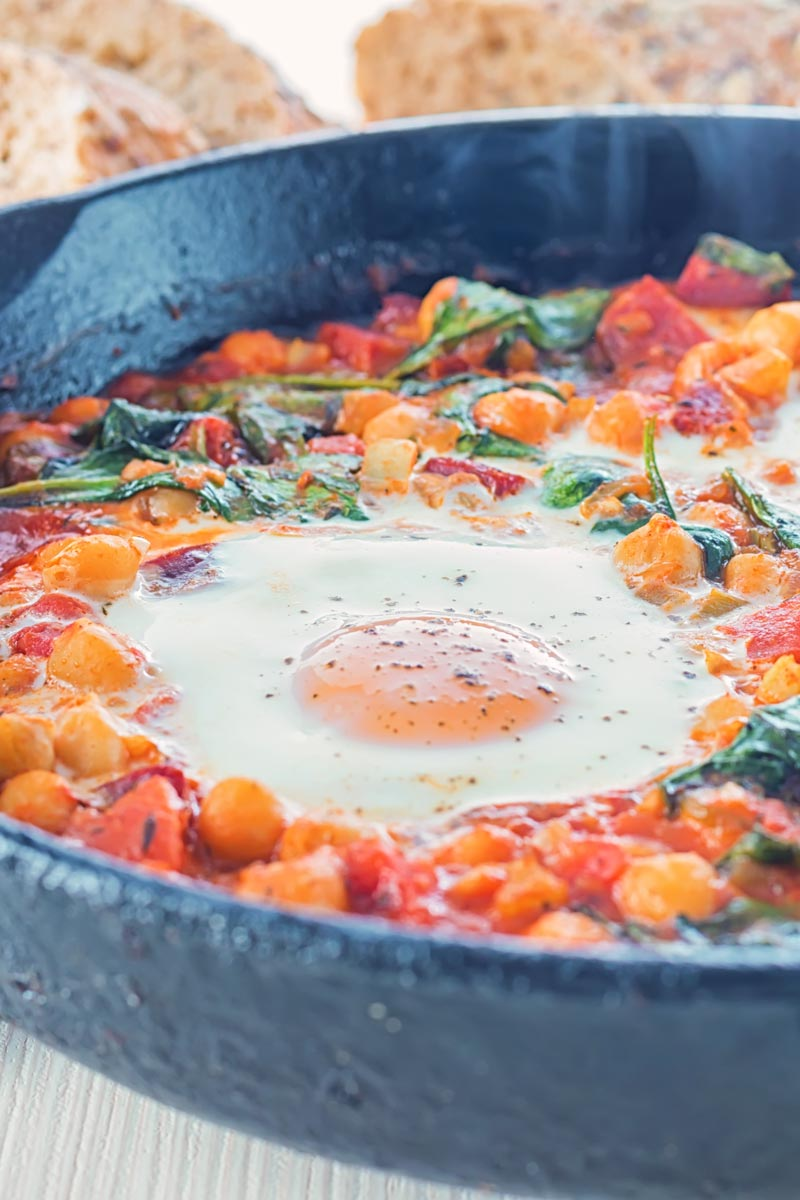Close up portrait image of eggs in a tomato sauce and baked chickpeas served and cooked in a cast iron skillet