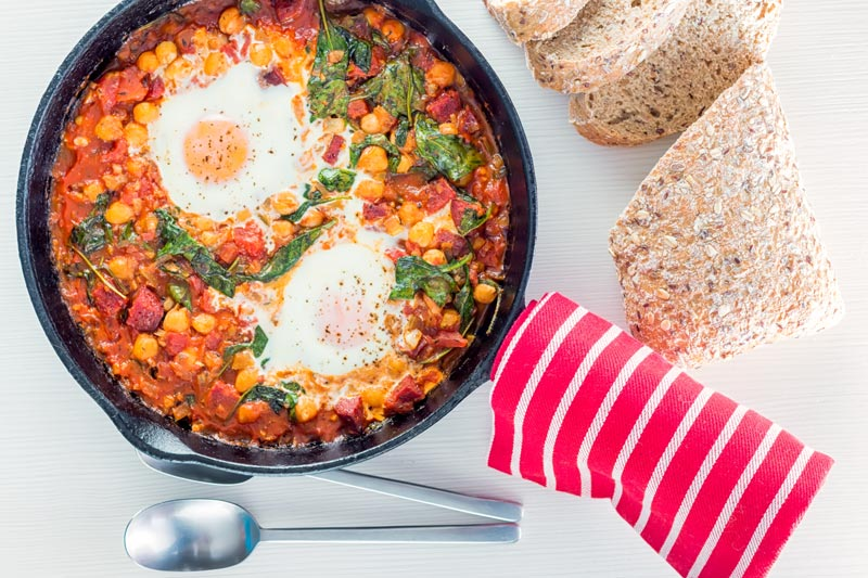 Overhead landscape image of baked chickpeas with tomato and eggs served and cooked in a cast iron skillet served with seeded bread