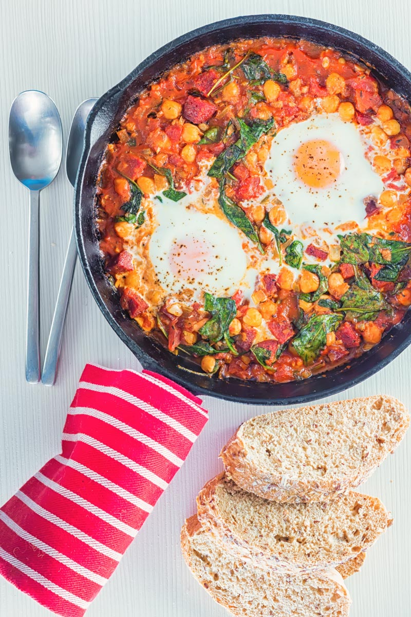 Overhead portrait image of baked chickpeas with tomato and eggs served and cooked in a cast iron skillet served with seeded bread